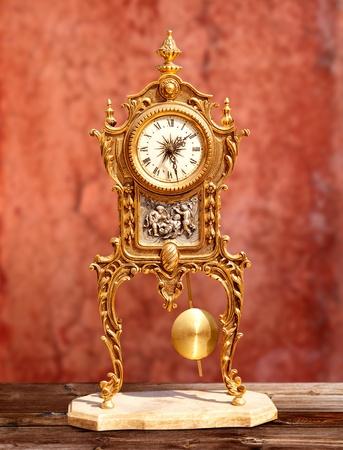 reloj de pendulo: �poca antigua de lat�n dorado reloj de p�ndulo en el fondo rojo del grunge Foto de archivo