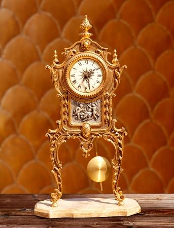 ancient vintage golden brass pendulum clock  in embossed background Stock Photo - 10743033