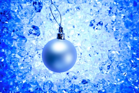 christmas silver bauble on blue winter ice background photo