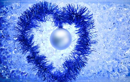 christmas silver bauble tinsel heart shape on blue winter ice photo