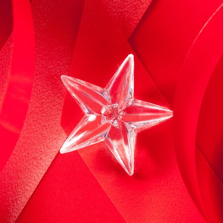 christmas glass star on red ribbon background photo