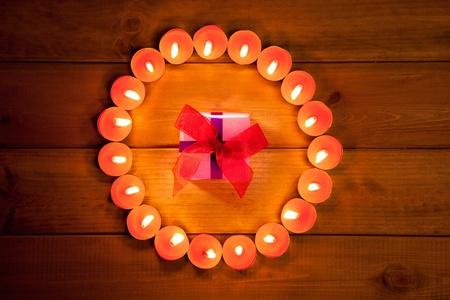 christmas candles circle over wood and ribbon gift box symbol photo