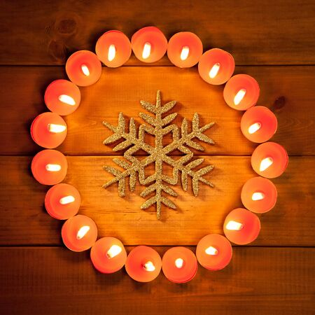 religious symbols: christmas candles circle over wood and golden snowflake symbol