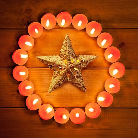 candle flame: christmas candles circle over wood and golden star symbol