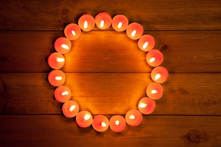 candles glowing in circle shape on golden wood background photo