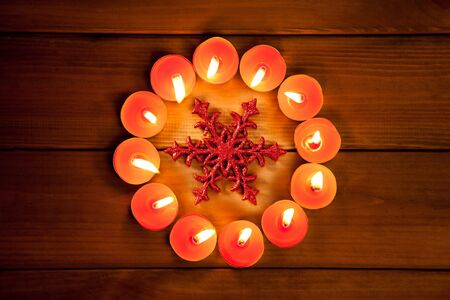 christmas candles circle over wood and red snowflake symbol photo