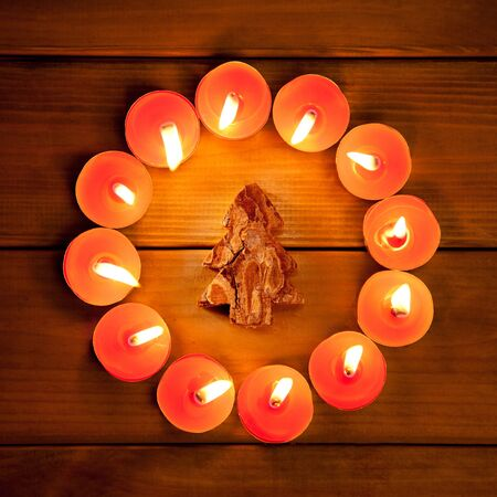christmas candles circle over wood and bark tree symbol photo
