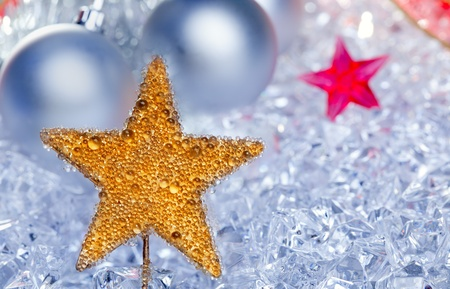 christmas golden star symbol with silver baubles and red ribbon on ice photo