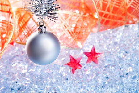 christmas silver bauble and red ribbon on ice with red star photo