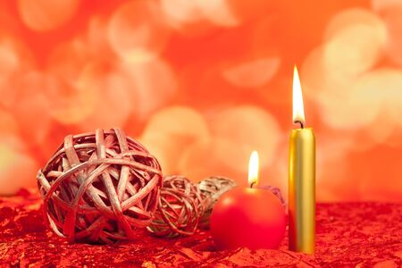 christmas candles with dried baubles on red lights background photo