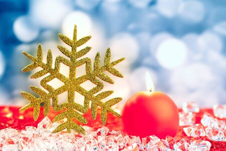 Christmas golden snowflake on ice cubes with blue lights bokeh background photo