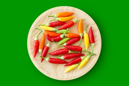 piquancy: colorful chili peppers plate isolated on green background Stock Photo