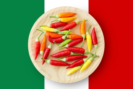 american cuisine: colorful chili peppers plate with Mexico flag in background