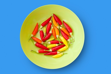 piquancy: colorful chili peppers plate isolated on blue background
