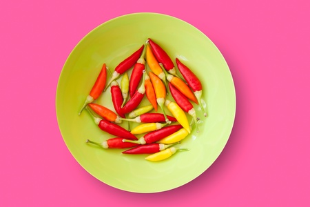 piquancy: colorful chili peppers plate isolated on pink background Stock Photo