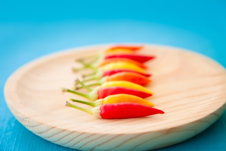 piquancy: colorful hot chili peppers in a row on wooden plate