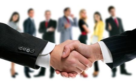 saludo de manos: gente de negocios apret�n de manos con el equipo de la compa��a en el fondo