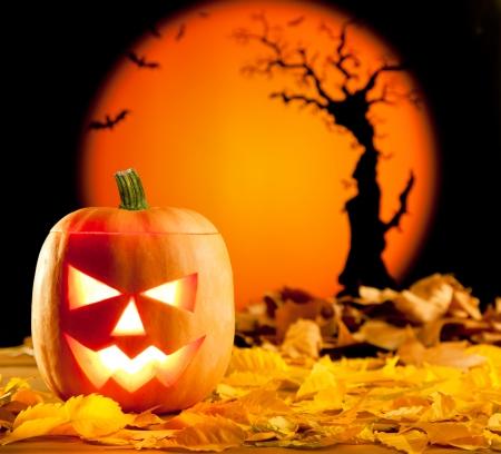 tallado en madera: Naranja linterna de calabaza de Halloween con hojas de otoño