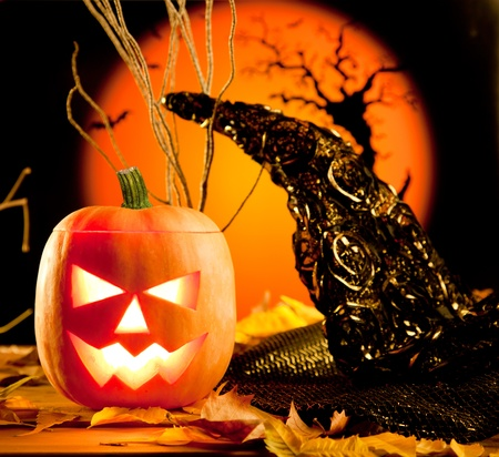 Halloween orange pumpkin lantern with autumn leaves photo