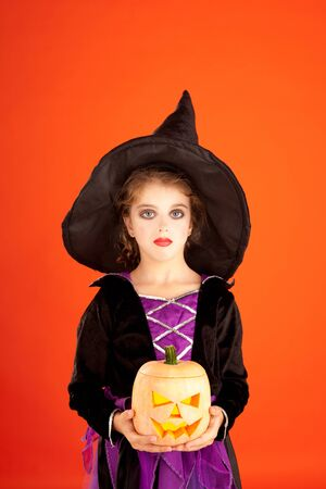 Halloween kid girl costume on orange background photo