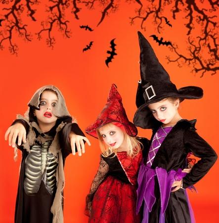 Halloween group of children girls costumes on orange background photo