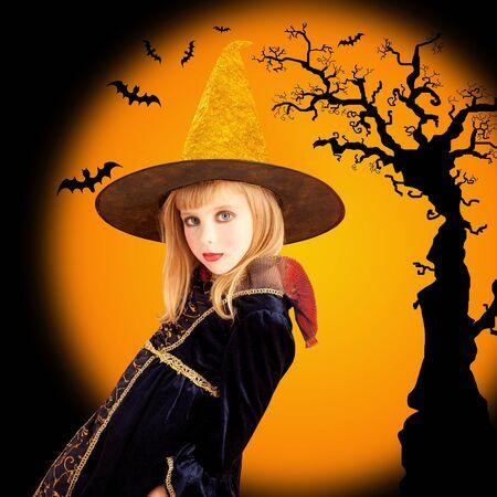 Halloween beautiful girl in dried tree and bat orange background photo