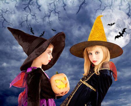 Halloween kid girls and pumpkin on cloudy moon sky photo