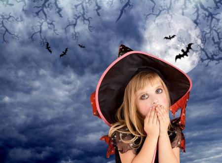 Halloween scared kid girl on dark sky and moon with bat photo