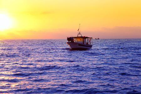 blue sea sunrise with sun in horizon with fishing boat sailing photo