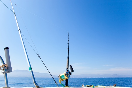 fishing boat trolling with outrigger gear and golden reel rod photo