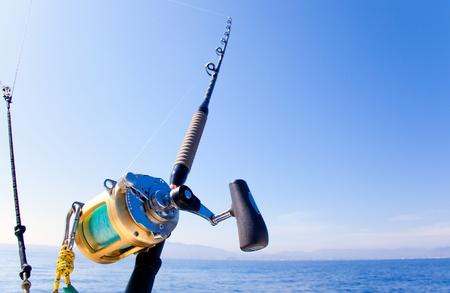 bateau de peche: bateau de pêche à la traîne dans l'océan avec tige de bobine d'or Banque d'images