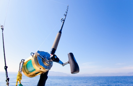 big game fishing: fishing boat trolling in ocean with golden reel rod