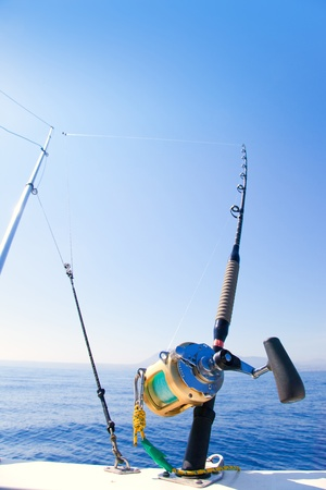 outrigger: fishing boat trolling with outrigger gear and golden reel rod Stock Photo