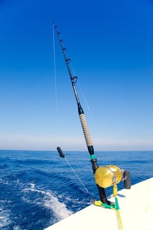 deep sea fishing: fishing boat trolling in ocean with golden reel rod