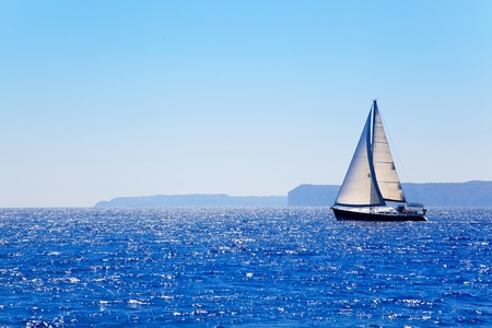 Blue Mediterranean sailboat sailing in perfect ocean at San Antonio cape Stock fotó