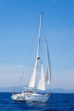 Blue Mediterranean sailboat sailing in perfect ocean photo
