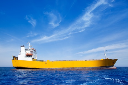 Anchor cargo yellow boat in blue sea under summer sky Stock Photo