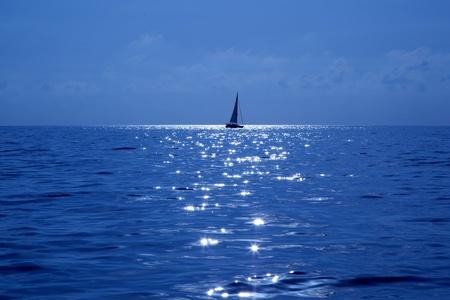 blue sailboat sailing mediterranean sea with water horizon photo