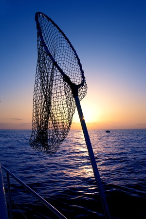 fishing catches: dip net in boat fishing on sunrise water horizon