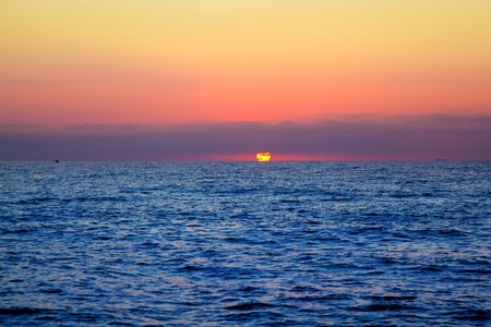 sunrise ocean: blue sea sunrise with sun in horizon and red sky