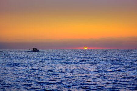 deep orange: blue sea sunrise with sun in horizon with fishing boat sailing Stock Photo