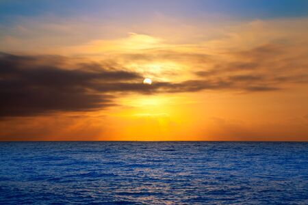 golden sunrise with sun and clouds over blue Mediterranean sea