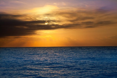 golden sunrise with sun and clouds over blue Mediterranean sea photo