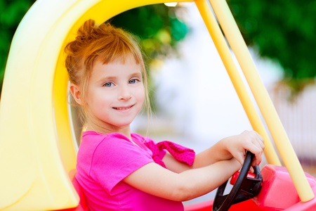 children playing with toys: blond children girl driving toy car yellow Stock Photo