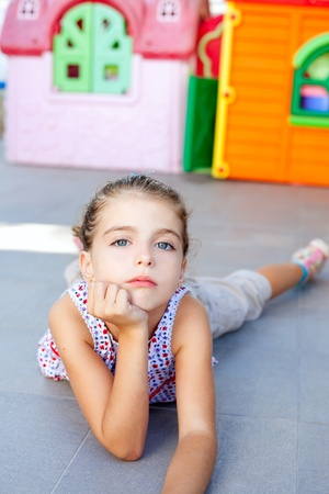 beautiful little serious girl lying on floor in playground photo
