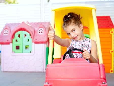 children girl driving a toy car with ok hand gesture in playground photo