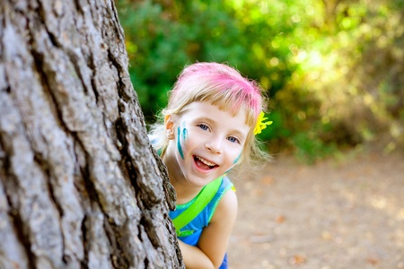 'hide out': children little girl happy playing in forest tree with party makeup