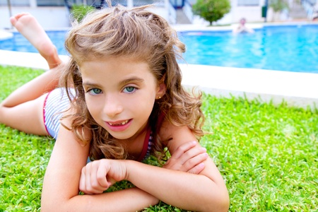 children girl lying on grass in pool during summer vacation photo