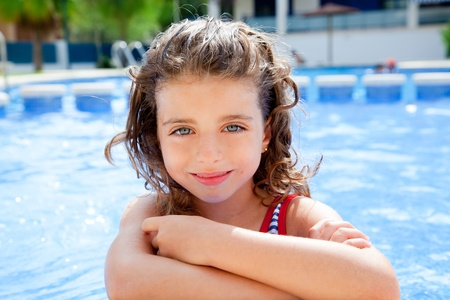 happy kid girl smiling at swimming pool in summer vacation photo