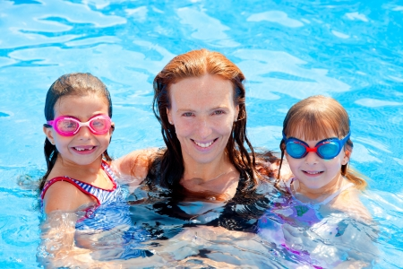 daughters and mother family swimming in pool on summer vacation